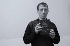 Senahid Halilovic holding the book he has written about surviving the genocide in Bosnia